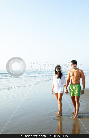 couple walking along the seashore stock photo, portrait of a  cute couple walking along the seashore by pablocalvog