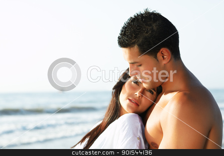 loving couple looking at the horizon stock photo, close up portrait of a  loving couple looking at the horizon from the shore of the beach by pablocalvog