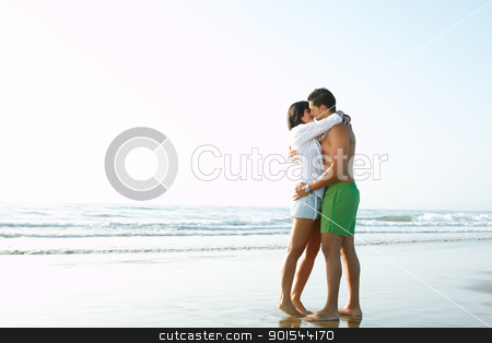 adorable  couple in love kissing and embracing each other stock photo, portrait of an adorable  couple in love kissing and embracing each other on the edge of the beach by pablocalvog