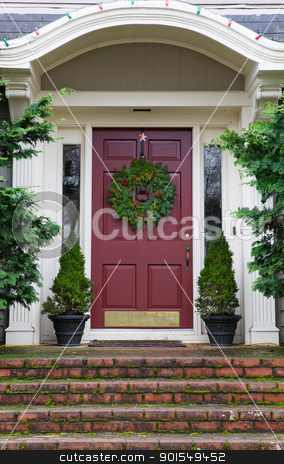 Magenta Door with Wreath stock photo, Magenta Door with Wreath on gray home with mossy red brick steps by bobkeenan