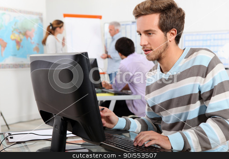 Young man working at a computer stock photo, Young man working at a computer by photography33