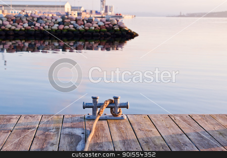 Cleat on a pier stock photo, Metal cleat with a rope on a pier by Nanisimova