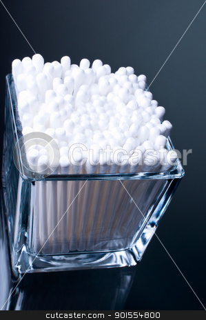 Cotton buds in glass dark background stock photo, Cotton buds in a glass on a glass table on a dark background by Nanisimova