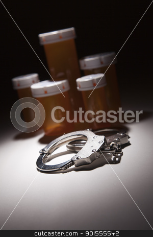 Handcuffs, Medicine Bottle and Pills Under Spot Light stock photo, Handcuffs, Medicine Bottle and Pills Under Spot Light Abstract. by Andy Dean