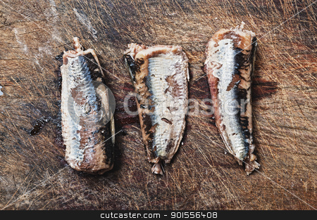 Fresh sardines on wooden background.  stock photo, Three fresh sardines on wooden table.  by Pablo Caridad