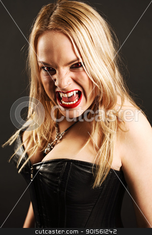 Female vampire stock photo, Photo of a female vampire with mouth open and fangs showing.  Harsh lighting and shadows for scarier feel. by © Ron Sumners
