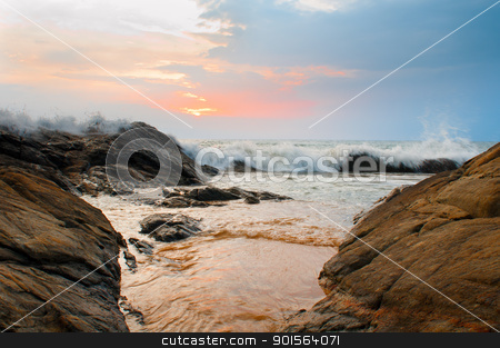Beautiful stones and waves at sunset stock photo, Beautiful stones and waves at sunset under blue sky by Iryna Rasko