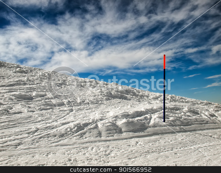 Skiing stock photo, Detail of the ski slope with a marking stick under blue sky with clouds.. by Sinisa Botas