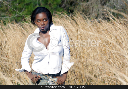 Beautiful Woman Outdoors in Tall Grass (10) stock photo, A lovely young black woman outdoors, standing in tall grass.  Generous copyspace on frame right. by Carl Stewart