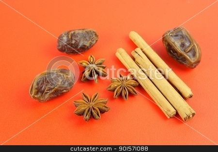 Christmas baking: Cinnamon, star anise, dates on red background stock photo, Three spices traditionally used for Christmas cookies and cakes placed on a warm red background: Star anise (Illicium verum), Cinnamon sticks (Cinnamomum verum) and Medjoul dates (Phoenix dactylifera).  by TheOrganic