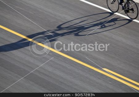 bike, road and shadow stock photo, abstract bicyclist shadow on an asphalt highway with yellow line by Marek Uliasz