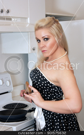 Beautiful Blonde in the Kitchen (1) stock photo, A lovely, glamorous young blonde stands at the stove with a spatula in hand. by Carl Stewart