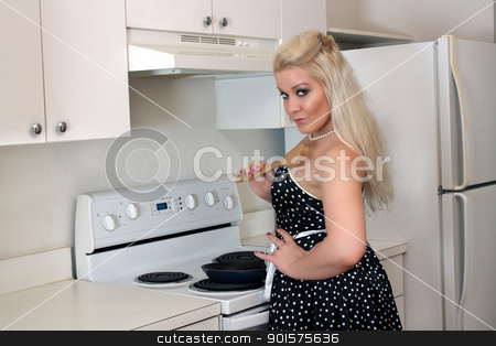 Beautiful Blonde in the Kitchen (5) stock photo, A lovely, glamorous young blonde stands at the stove with a spatula in hand. by Carl Stewart