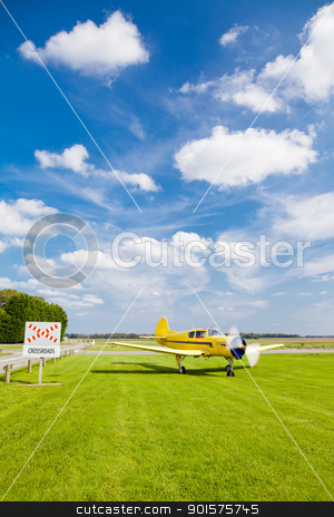 Plane at Crossroads stock photo, An old propeller plane yellow near a crossroads by Fred DE BAILLIENCOURT
