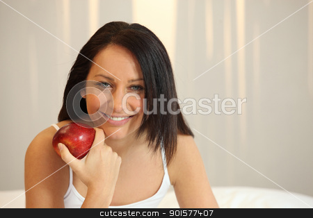 Woman with a red apple in bed stock photo, Woman with a red apple in bed by photography33