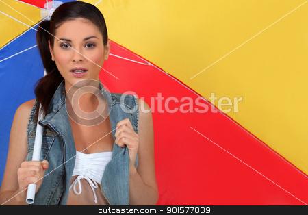 Woman carrying a beach umbrella stock photo, Woman carrying a beach umbrella by photography33