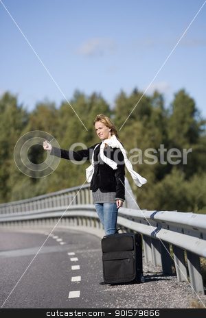 Hitchhiking woman stock photo, Hitchhiking woman alone at the side of the road by Anne-Louise Quarfoth