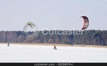 Kiteboarding with snowboards frozen lake in winter  stock photo, Kiteboarding with snowboards on frozen lake in winter. Active and modern people leisure.  by sauletas