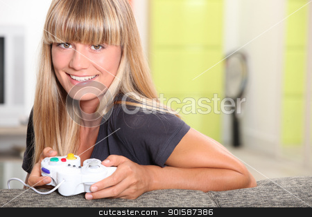 Blonde girl playing with console stock photo, Blonde girl playing with console by photography33