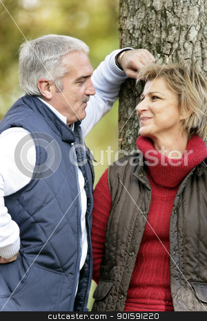 Loving couple standing by a tree stock photo, Loving couple standing by a tree by photography33