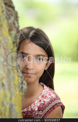 A little Latina hiding behind a tree. stock photo, A little Latina hiding behind a tree. by photography33
