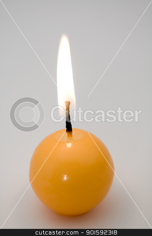 candle stock photo, small yellow burning candle, grey background by Robert Remen