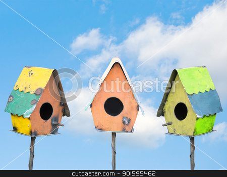 Bird Houses under a Blue Sky stock photo, Three colorful bird houses under a sunny blue sky by Leslie Murray