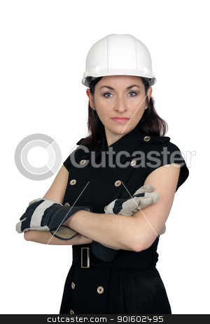 Beautiful Female Construction Worker (3) stock photo, A lovely brunette wearing a white hardhat, work gloves, and a snappy dress, with her arms crossed.  Isolated on a white background. by Carl Stewart
