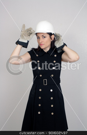 Beautiful Female Construction Worker (5) stock photo, A lovely brunette wearing a white hardhat, work gloves, and a snappy dress, isolated on a textured grey background with generous copyspace. by Carl Stewart