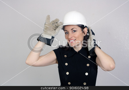 Beautiful Female Construction Worker (6) stock photo, A lovely brunette wearing a white hardhat, work gloves, and a snappy dress, isolated on a textured grey background with generous copyspace. by Carl Stewart