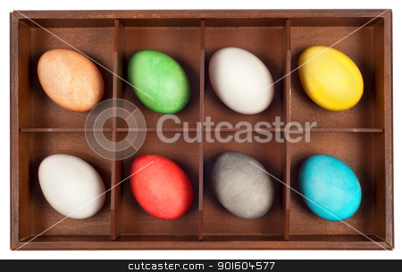 Easter Eggs in wooden box stock photo, Collection of multicolored easter eggs arranged  in a grunge wooden box.Isolated on white background by borojoint