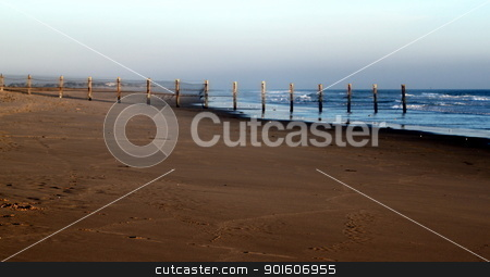 Beach Fence stock photo, sunset at Ormond Beach with beautiful sky and blue water by Henrik Lehnerer