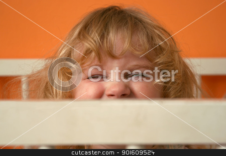 Girl face expression stock photo, Small girl with funny face expression behind fence of bed by vaximilian