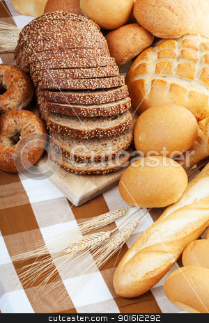 Baked bread stock photo, Assortment of baked bread on a table cloth by Steve Mcsweeny