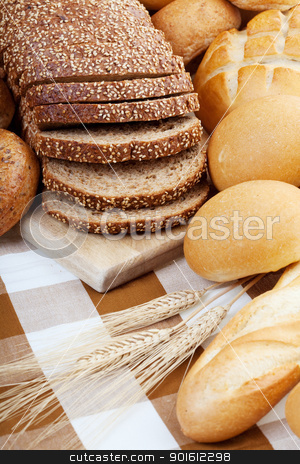 Bread assortment  stock photo, Assortment of baked bread with focus on the sliced loaf. by Steve Mcsweeny