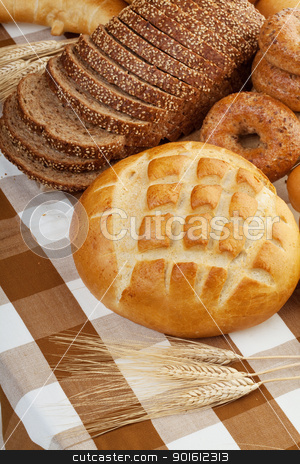 fresh baked bread stock photo, Assortment of baked bread on a table cloth  by Steve Mcsweeny