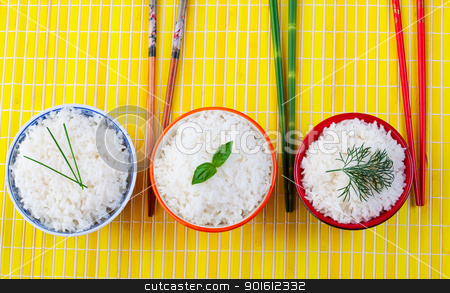 Rice bowls stock photo, Three bowls of rice with chopsticks on a yellow place mat by Steve Mcsweeny