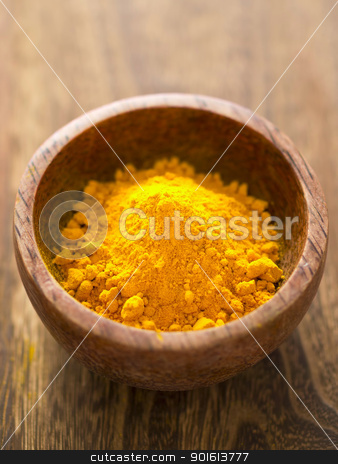 grounded turmeric stock photo, close up of a bowl of grounded turmeric by zkruger