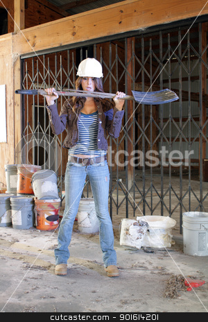 Beautiful Young Construction Worker (2) stock photo, A lovely young brunette wearing a hardhat with workboots, holding a plastic shovel with a broken handle, stands amidst the clutter of a long-abandoned warehouse. by Carl Stewart