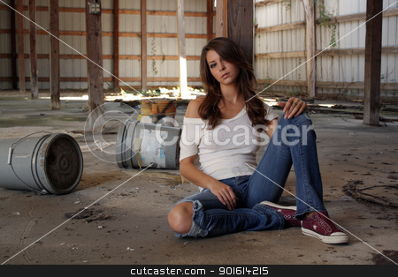 Beautiful Brunette Sitting in an Abandoned Warehouse (2) stock photo, A lovely young brunette in dress-down casual wear appears to be depressed as she sits on the floor of a long-abandoned warehouse. by Carl Stewart