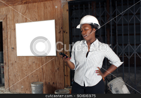 Lovely Female Construction Admin (2) stock photo, An attractive black woman wearing a white hardhat talks on her cell phone.  Beside and behind her is a white board on the wall where you can place your text or graphics. by Carl Stewart