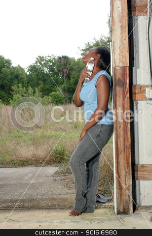Pretty Casual Woman with Bottled Water (3) stock photo, A lovely young black woman in casual wear cools off with a bottle of water. by Carl Stewart
