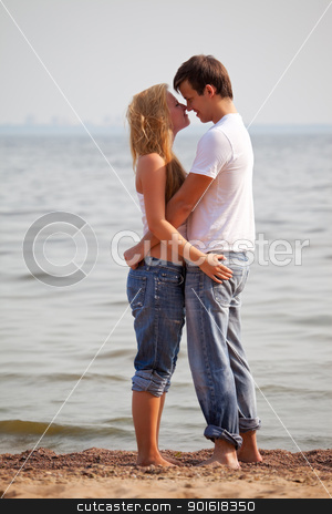 young couple on beach stock photo, young couple embrace on a sunny beach by Petr Malyshev