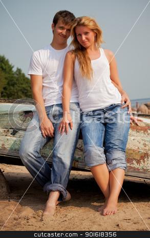 couple on a beach near old boat stock photo, beautiful couple on a beach near old boat by Petr Malyshev