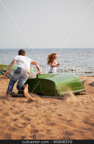 young couple fun stock photo, young couple fun and run around old boat on a beach by Petr Malyshev
