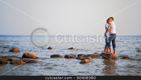 couple embrace on a stone in sea stock photo, beautiful couple embrace on a stone in sea by Petr Malyshev