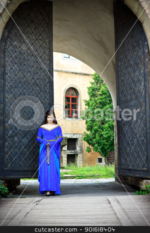 medieval girl on street of old town stock photo, medieval girl on street of old town near big gates by Petr Malyshev
