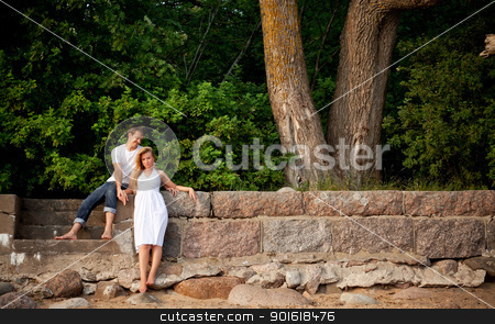 couple stand next stonewall in forest stock photo, young couple stand next stonewall in forest by Petr Malyshev
