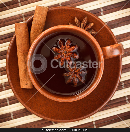 tea with cinnamon sticks and star anise stock photo, cup of winter tea with cinnamon and star anise on bamboo napkin by Petr Malyshev