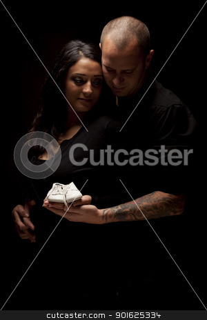 Mixed Race Couple Holding New White Baby Shoes on Black stock photo, Mixed Race Couple Holding New White Baby Shoes Against a Black Background Under Dramatic Lighting. by Andy Dean